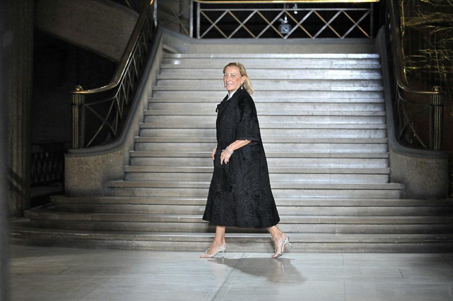 Miuccia Prada trägt auch eine Uniform, allerdings ihre eigene: Midi-Rock, Heels, Statement-Schmuck und körperferne Silhouetten