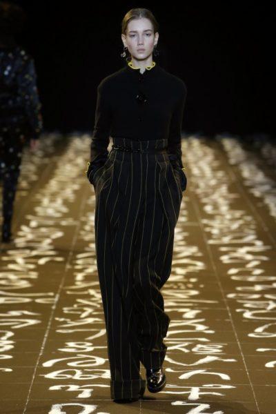 Edun: Kombination aus weiter Hose im Paperbag-Style mit Strickcardigan – beides in Schwarz/Gelb.