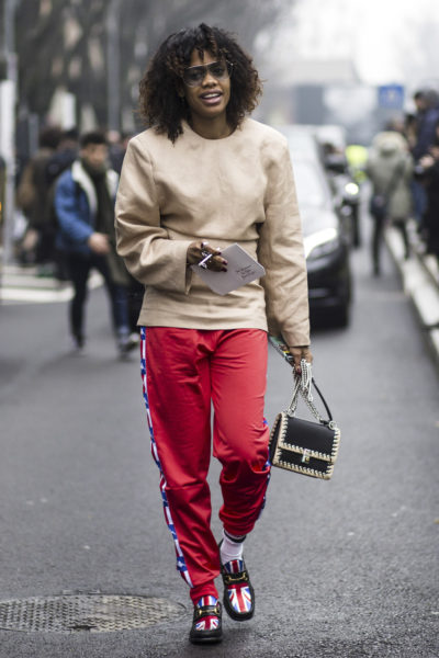 Jan Quammie wears Gucci loafers, trousers by Kappa, a top by Jil Sander and bag by Fendi