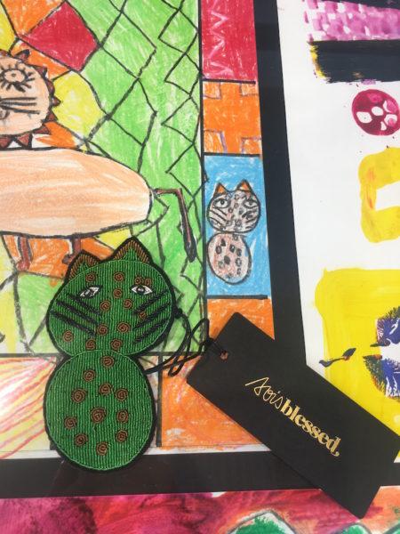 Handgestickte Katzenbrosche nach Vorlage einer Kinderzeichnung aus der Hope School – gesehen bei Sois Blessed in der Prannerstraße 10, München