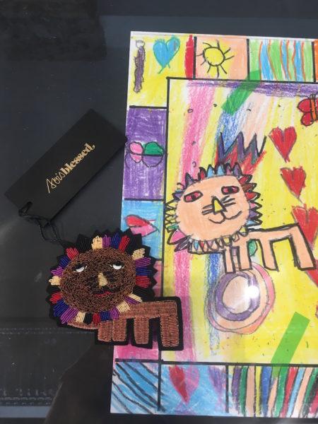 Handgestickte Löwenbrosche (Metallfäden auf Filz, circa 79 Euro) nach Vorlage einer Kinderzeichnung aus der Hope School – gesehen bei Sois Blessed in der Prannerstraße 10, München