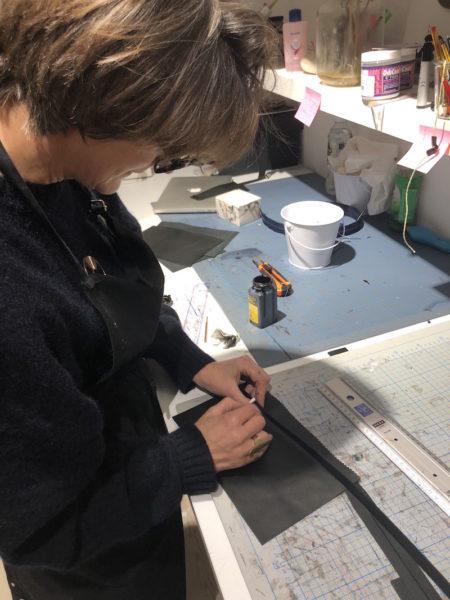 Justine Nessi bestreicht die Kanten eines Handtaschen-Umhängeriemens