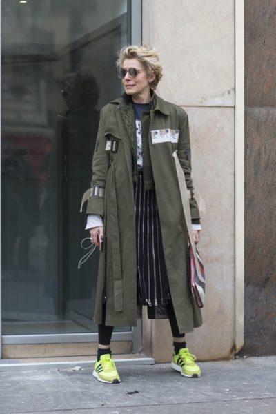 Rose Langenbein trägt einen Mantel von Dunst, ein Jackett von Haider Ackermann, einen Rock von Loewe und Sneaker von Adidas