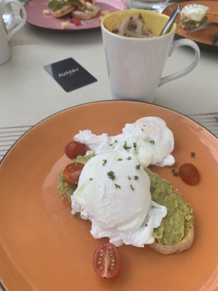 Eggs Benedict auf Avocado-Toast und Cappuccino zum Frühstück